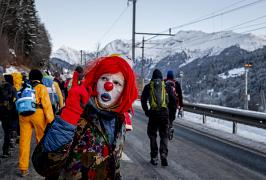 A man dressed as a clown is part of hundreds of climate protesters who are on a three-day protest march from Landquart to Davos pass the city of Klosters, Switzerland.