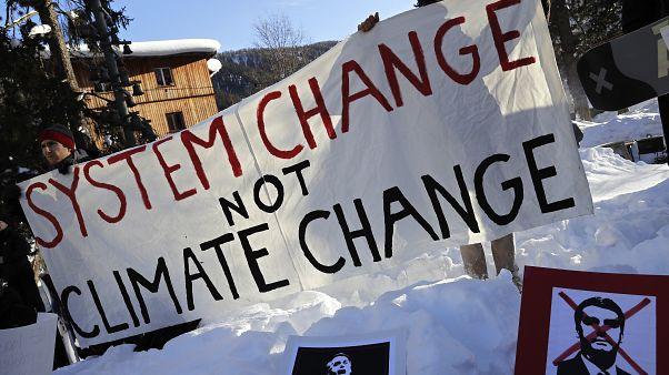 متظاهرون يحملون لافتة خلال احتجاج خارج الاجتماع السنوي للمنتدى الاقتصادي العالمي في دافوس بسويسرا