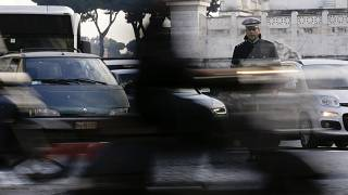 A City Police officer stands among cars as he directs traffic in downtown Rome, Thursday, Dec. 24, 2015.