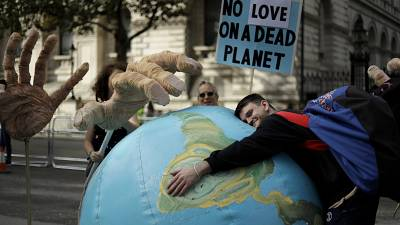 An Extinction Rebellion climate change protester hugs an inflatable planet Earth near Downing Street in London.