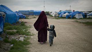 إمرأة تمشي مع إبنها في مخيم في شمال سوريا