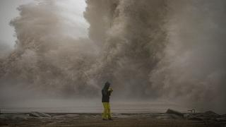 A woman photographs the Mediterranean sea as the waves hit the breakwater during a storm in Barcelona, Spain, Tuesday, Jan. 21, 2020.