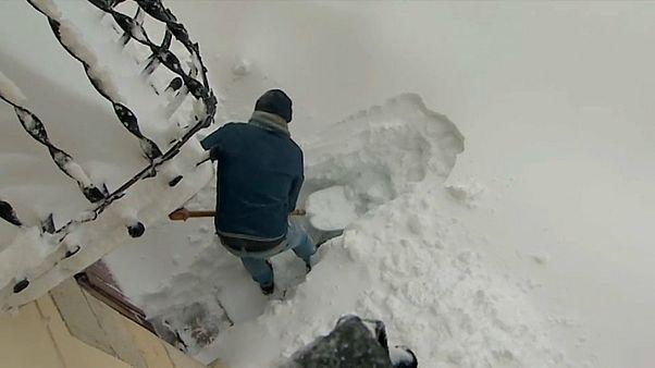 Mann schüppt Schneemassen vor seinem Haus