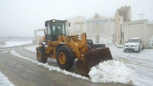 جرافة تزيل الثلوج من أحد الشوارع بالأردن