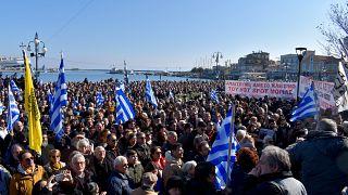 Κόσμος κρατώντας σημαίες και πανό συμμετέχει στη συγκέντρωση διαμαρτυρίας για το μεταναστευτικό