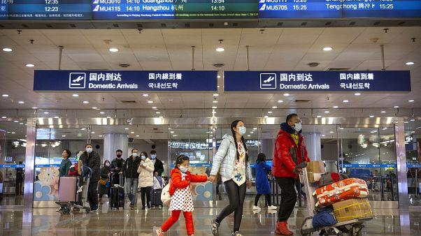 Pekin Uluslararası Havaalanı'ndaki yolcular da virüse karşı maske taktı