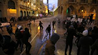 Anti-government protesters clash with the riot police during ongoing protests in Beirut, Lebanon, Wednesday, Jan. 22, 2020.