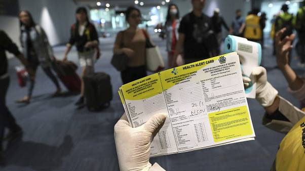 A health official holds a health alert card at the Soekarno-Hatta International Airport in Tangerang, Indonesia, Wednesday, Jan. 22, 2020