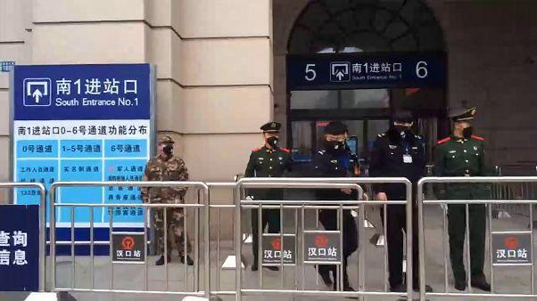 Agentes de seguridad frente a una estación de tren de Wuhan, la ciudad donde se originó el brote