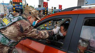 Contrôle de température par la police paramilitaire sur une barrière de péage d'une autoroute de Wuhan, le 23 janvier 2020.