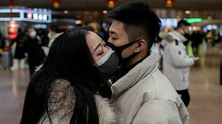 Çin'in başkenti Pekin'deki tren istasyonunda birbirine veda eden bir çift. Yetkililer tüm vatandaşları maske takmaları konusunda uyarıyor