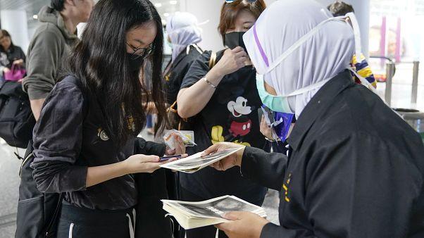 Agentes de inmigración dan información a viajeros en el aeropuerto de Kuala Lumpur
