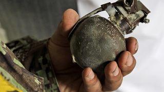 Afgan askeri el bombasını tutuyor