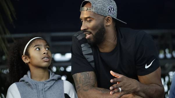 In this July 26, 2018 file photo former Los Angeles Laker Kobe Bryant and his daughter Gianna watch the U.S. national championships swimming meet in Irvine, Calif.