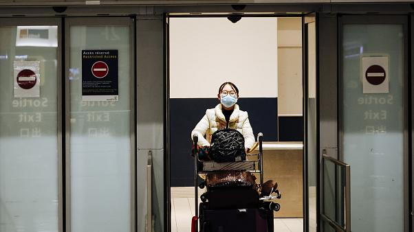 A traveler coming from Beijing and wearing a mask arrives at Charles de Gaulle airport, Paris.