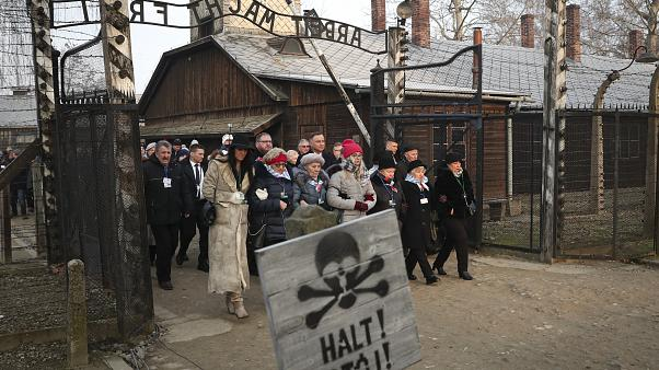 Poland's President Andrzej Duda walks with survivors through the gates of Auschwitz the 75th anniversary of its liberation Monday, Jan. 27, 2020.