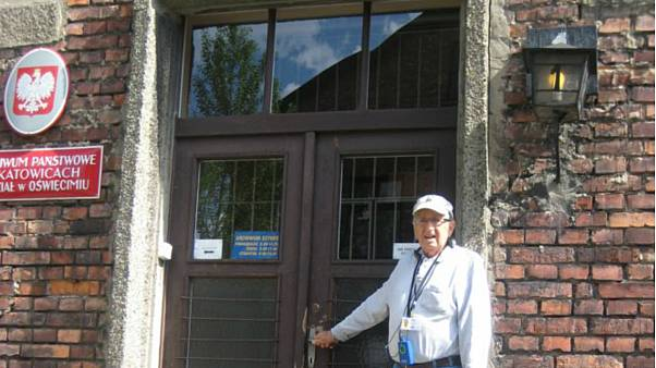 Siegmund Listwa, a Holocaust survivor, stands in front of his housing unit in Auschwitz, 2014.