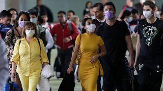 مسافرون يرتدون أقنعة عند وصولهم إلى مطار مانيلا الدولي في الفلبين.