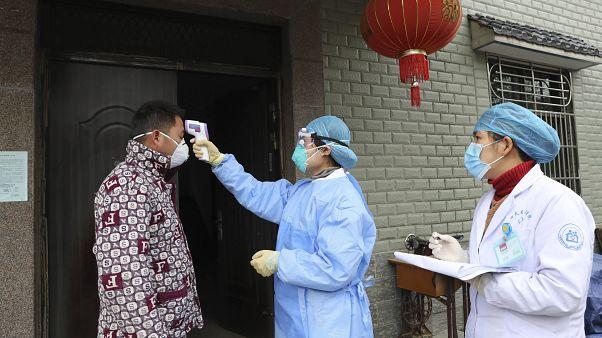 مسؤولو الصحة في الصين يقيسون درجة حرارة شخص للتأكد من عدم إصابته بفيروس كورونا