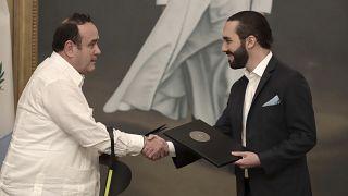 El presidente de Guatemala, Alejandro Giammattei, y el de El Salvador, Nayib Bukele, se dan la mano tras firmar el acuerdo