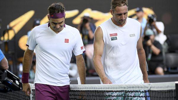 Roger Federer, left, walks with Tennys Sandgrenafter winning their quarterfinal match at the Australian Open tennis championship in Melbourne, Australia