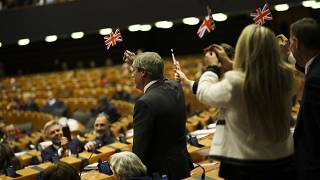 British European Parliament member Nigel Farage, left, and other pro-Brexit British MEP's wave the Union flags.
