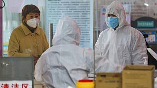 Medical workers in protective gear talk with a woman suspected of being ill with a coronavirus at a community health station in Wuhan in central China's Hubei Province