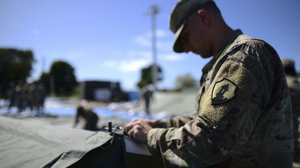 أحد أفراد احتياطي الجيش الأمريكي يعمل على إعداد وحدات دش محمولة في مدينة خيام لمئات الأشخاص النازحين بسبب الزلازل في غوانيكا ، بورتوريكو ، الثلاثاء ، 14 يناير ، 2020