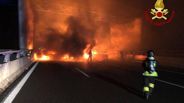 In this photo released by the Italian Firefighters, firemen try to extinguish a dozen vehicles on fire on a highway near Milan, Italy, in the early hours on Jan. 29.