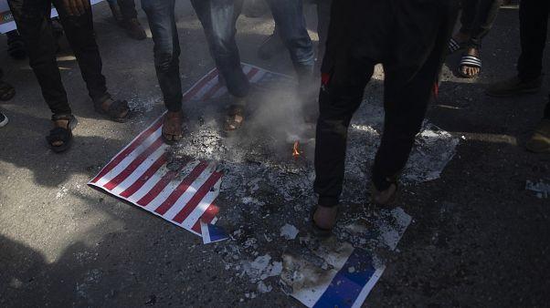 المتظاهرون الفلسطينيون يحرقون أعلاما إسرائيلية وأميركية أثناء الاحتجاج على خطة السلام الأمريكية في الشرق الأوسط في مدينة غزة / 28 يناير 2020