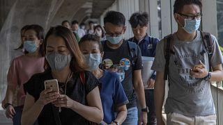 Tayland'da koronavirüse karşı maske takan insanlar