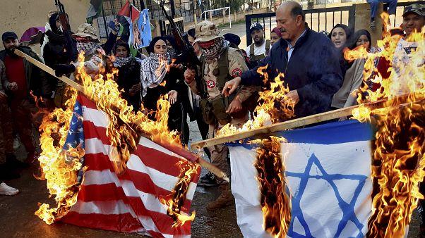 فلسطينيون مسلحون ومدنيون يحرقون علمي إسرائيل والولايات المتحدة خلال احتجاج في مخيم عين الحلوة في لبنان