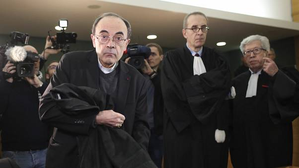 Cardinal Philippe Barbarin takes his seat as he arrives at the Lyon courthouse with his lawyers to attend his trial, in Lyon, Monday Jan. 7, 2019