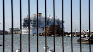 The Costa Smeralda cruise ship is seen behind a fence at it is docked in the Civitavecchia port on January 30, 2020