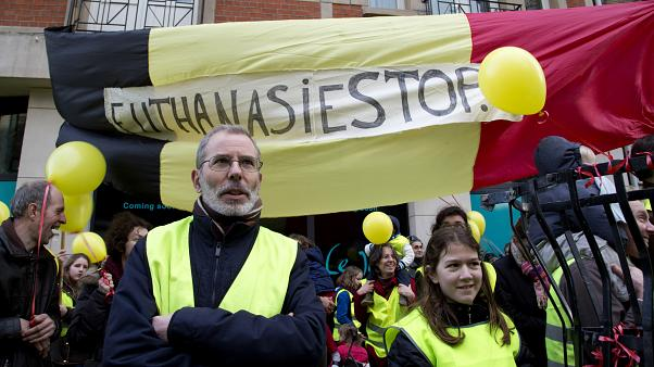 """protestors stand in front of a banner which reads """"Euthanasia Stop"""", during an anti-euthanasia demonstration in Brussels in February 2014."""