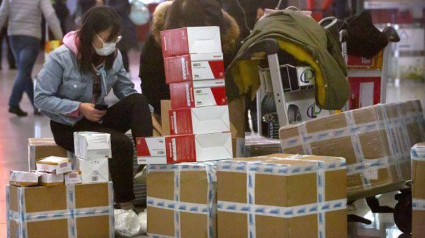 Женщина сидит рядом с коробками с медицинскими масками.