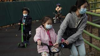 Children wearing masks, play in a park in Hong Kong, Friday, Jan. 31, 2020