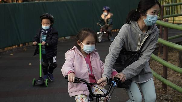 Children wearing masks, play in a park in Hong Kong, Friday, Jan. 31, 2020