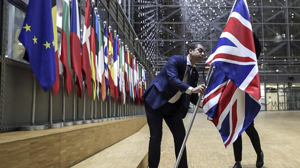 A member of protocol removes the Union flag from the atrium of the Europa building in Brussels, Friday, Jan. 31, 2020.