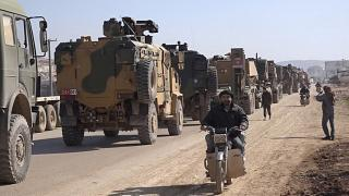 Screenshot - Sunday, Feb. 2, 2020, people ride their motorcycles next to a Turkey Armed Forces convoy is seen at the northern town of Sarmada, in Idlib province, Syria.