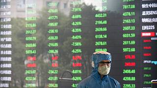 Ein Arbeiter mit Maske in der Börse in Shanghai