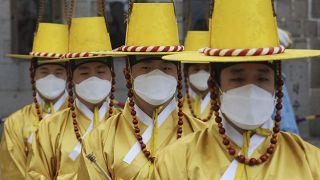 Güney Kore'nin Seul kentinde imparatorluk muhafızları, Deoksu Sarayı önünde Kraliyet Muhafızları Değiştirme Töreni canlandırması sırasında yüz maskesi takıyor