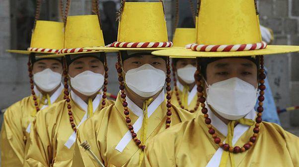 سربازان گارد امپراطوری در برابر کاخ سلطنتی کرهٔ جنوبی واقع در سئول ماسک تنفسی بر چهره دارند