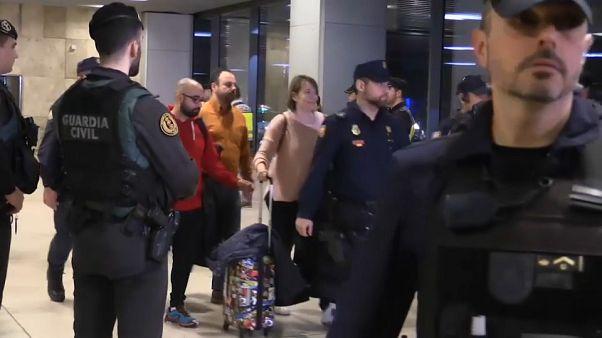 عناصر الأمن ترافق ركاب الطائرة إثر نزولهم في مطار مدريد.
