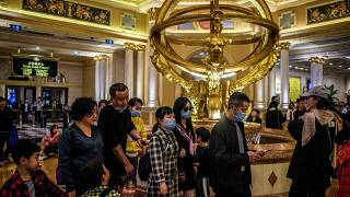 This file photo taken on January 22, 2020 shows visitors wearing face masks as they walk inside the Venetian casino hotel resort in Macau.