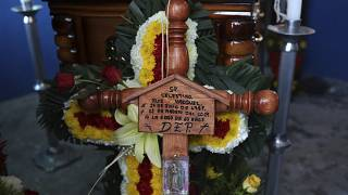 A cross bearing the name of Mexican journalist Jorge Celestino Ruiz Vazquez is displayed near the coffin containing his remains in Actopan, Veracruz, Saturday, Aug. 3, 2019