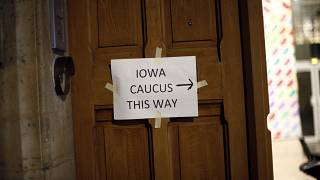 A placard reading « Iowa Caucus this way » hangs on a door, in Paris on Feb. 3, 2020. Paris is one of just three satellite caucus locations outside the U.S.