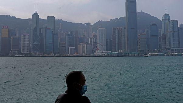 Hong Kong'un Victoria Harbour kıyısında maske giyen bir adam