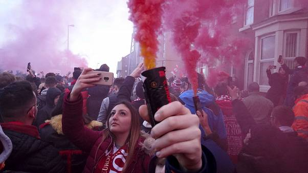 Football supporters set off flares before the English Premier League soccer match between Liverpool and Manchester United near Anfield Stadium in Liverpool.