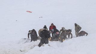 Security officers and villagers carry a victim of an avalanche near the town of Bahcesehir, in the eastern Turkey province of Van, on February 5, 2020.